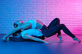 Pretty two young slim gymnast women in sports clothing stretching in front of brick wall in neon lights. Flexible muscular women doing gymnastic exercise.