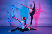 Pretty two young slim gymnast women in sports clothing stretching in front of brick wall in neon lights. Flexible muscular women doing gymnastic split with ball and ribbon.