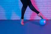 Close up photo of young slim gymnast woman legs in sports clothing exercises with ball in front of brick wall in neon lights.