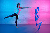 Pretty young slim gymnast woman in sports clothing stretching in front of brick wall in neon lights. Flexible muscular woman doing spirals with ribbon.