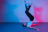 Charming young slim gymnast woman in sports clothing exercises in front of brick wall in neon lights. Flexible fit woman doing exercise with ball.
