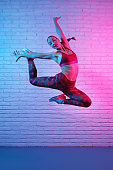 Charming young slim gymnast woman in sports clothing exercises in front of brick wall in neon lights. Flexible muscular woman doing gymnastic elements.