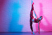 Young slim gymnast woman in sports clothing stretching on brick wall in neon lights.