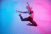 Charming young slim gymnast woman in sports clothing exercises in against brick wall in neon lights. Flexible muscular woman doing gymnastic elements.