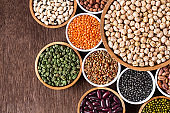 Various assortment of indian legumes in bowls - beans, chickpeas, lentils, dal top view.