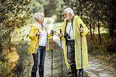 Senior couple in raincoats hiking in the forest