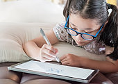 Asian school child girl using smart  tablet device digital technology drawing on innovative touchscreen surface