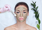 A beautiful woman makes a anti wrinkle mask on face.
