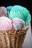 Balls of yarn for knitting. Balls of yarn for knitting in a wicker basket. Knitting thread. Colorful threads.
