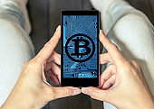 Woman using a mobile phone displaying a bitcoin wallet screen
