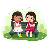 Two little girls eating ice cream on the bench.
