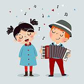 Cute boy playing on a musical instrument accordion and little girl singing.