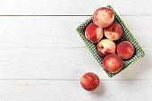 peaches in a straw basket on a wooden background.