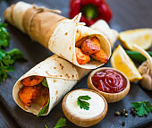 Grilled chiken wraps with ketchup ans cream sauces, tasty clasic tortilla wraps with chicken meat and vegetables