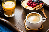 Breakfast meal with cup of coffee, glass of orange juice and a bowl of oatmeal with fresh berries, banana and almonds