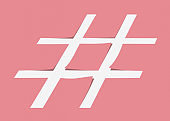 White hashtag symbol cut from pastel pink paper as a background.
