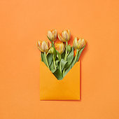 Post card with bouquet of tulips in craft envelope on an orange background.