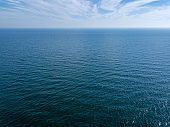 Panoramic view from drone endless blue seascape on a background of cloudy sky. Natural background. Copy space.