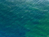 Aerial top view water surface background. Bird eye sea surface photo from drone. Turquoise ocean from above.