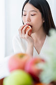healthy pretty asian woman happiness enjoy eat and love diet with red fresh apple fruit weight loss iedeas concept white room interior background