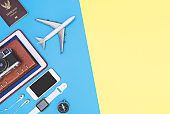 travel objects and accessories on blue yellow background with passport camera and plane