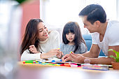 happiness lovely father mother teach homework for little preety daughter in living room family concept