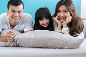 happy Asian Family mother father and daughter making a fun sleep play in living room home background.