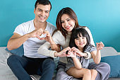 happy family father mother daughter play and enjoy tegether with love and care on white bed home concept