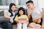 happiness asian family dad mom and daughter sit relax wachting tablet togehter home sweet home concept