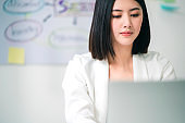 successful asian business offlce woman working with laptop with happiness and freshness emotion office background