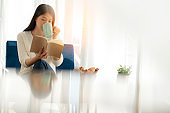 relax and peaceful asian woman enjoy vacation weekend with hot tea and good book morning time near window home background