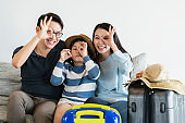 exited asian family mom dad daughter happiness trip travel concept with hand pose with luggage on sofa home background
