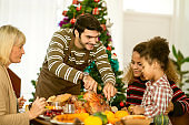 Happy American family communicating while having Thanksgiving lunch in dining room festive ideas concept