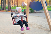 Happy child girl on swing in sunset fall. Little kid playing in the autumn on the nature park