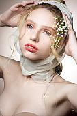Blue-eyed model wearing beige bra posing with flowers in hair
