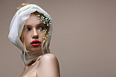 Model with white silk scarf on her head posing near background