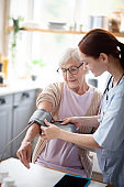 Retired woman watching nurse measuring blood pressure