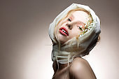 Young blue-eyed model posing with white silk scarf on head