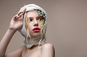 Blue-eyed model natural makeup posing with flowers in hair