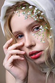 Blue-eyed young model posing with decorations on her head
