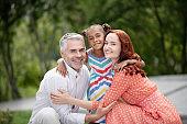 Loving foster parents hugging their lovely dark-skinned girl