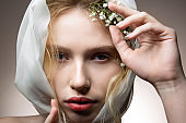 Model with thick eyebrows posing with white flowers in hair