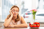 Woman having wish to eat tomatoes but suffering from allergy