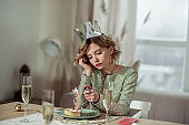 Birthday woman using lighter burning the candle on piece of cake