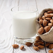 Milk or yogurt in drinking glass on white wooden table with almonds in hemp sack aside