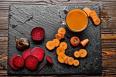 Top view at vegetable background of beets carrots and juice on kitchen table close up view