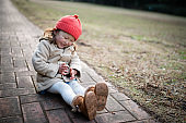 Toddler girl sitting on the sidewalk