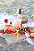 Picnic outdoor with rose wine fruits, meat and cheese