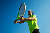 Male young tennis player ready to start a game holding his racket and a tennis ball