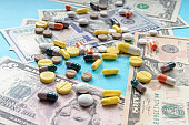 Colorful, variety pills and capsules on dollars banknotes. concept of high cost treatment, preservation of health and medical insurance